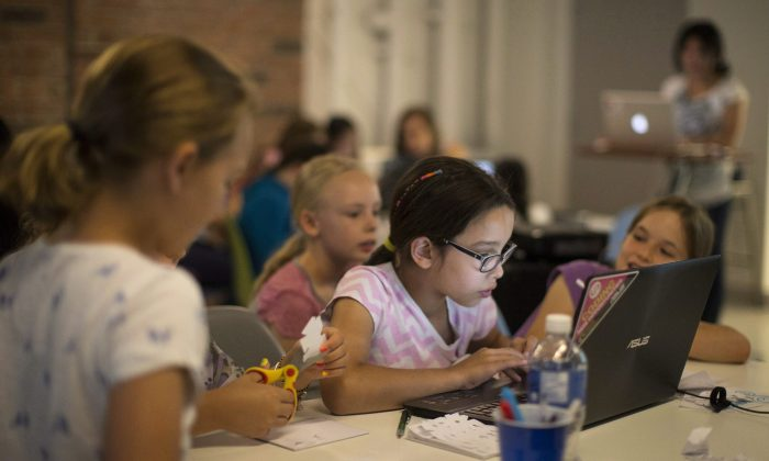 Girls learn about computers at an early age by attending a workshop in Toronto on July 16, 2014. The need to fill the skilled jobs required in the information and communications technology field means that it is important to encourage a greater percentage of young women to get involved. (The Canadian Press/Chris Young)