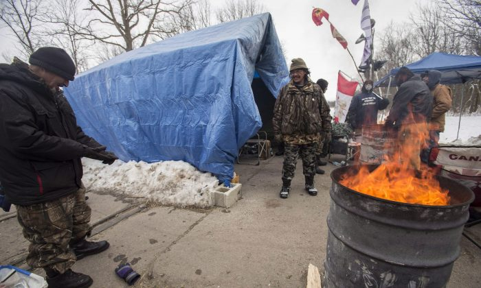 First Nations protesters continue their blockade of the CN tracks in Sarnia, Ont., on Jan. 2, 2013, after a court injunction to have them move was issued over the holidays. The protest, which blocked the tracks for 13 days, was mentioned as a concern in a federal analysis of protests in Canada. (The Canadian Press/ Geoff Robin)
