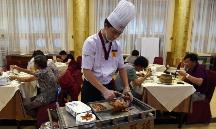A chef slices Peking duck for diners at the Quanjude restaurant in Beijing on July 24, 2014. Chinese local officials frequently dine in restaurants with the expectation that public funding will cover their expenses. (Greg Baker/AFP/Getty Images)