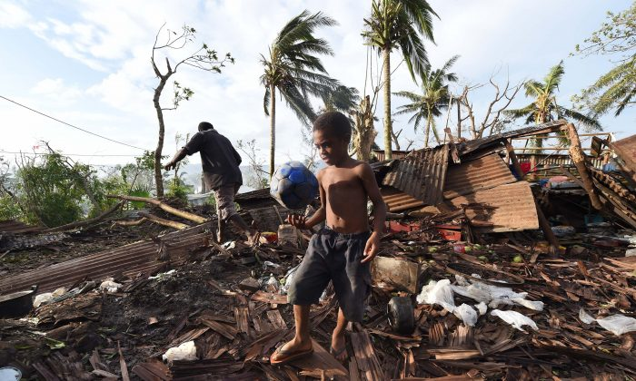 A local Vanuatu boy named Samuel walks through through the ruins of his family home with his father Phillip, in Port Vila on March 16, 2015.  (Dave Hunt-Pool/Getty Images)