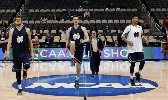 Notre Dame's Austin Burgett, left, Matt Gregory, center, and Zach Auguste, left, warm up during practice at the NCAA college basketball tournament in Pittsburgh, Wednesday, March 18, 2015. Notre Dame plays Northeastern in the second round on Thursday. (AP Photo/Keith Srakocic)
