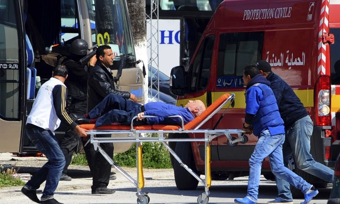 A man is evacuated outside the Bardo Museum after it was under attack  by gunmen in Tunis, Tunisia, on Wednesday, March 18, 2015. Authorities say scores of people are dead after an attack on a major museum in the Tunisian capital, and some of the gunmen may have escaped. (AP Photo/Salah Ben Mahmoud)