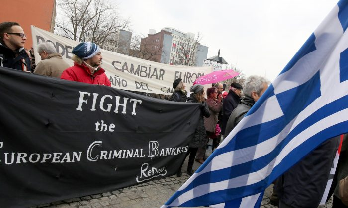 """Protesters hold a sign reading """"Fight the European Criminal Bankers"""" and a Greek flag in front of the German FINANCE Ministry in Berlin on March 14, 2015. (Wolfgang Kumm/AFP/Getty Images)"""