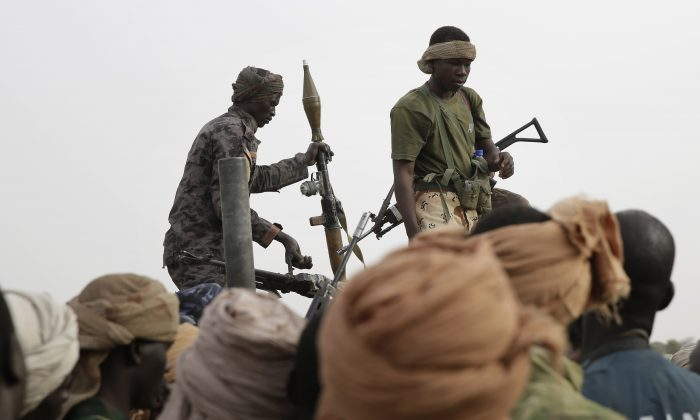 Chadian soldiers transfer weapons seized from Boko Haram fighters to a truck in the Nigerian city of Damasak, Nigeria, Wednesday March 18, 2015. Damasak was flushed of Boko Haram militants last week, and is now controlled by a joint Chadian and Nigerien force. (AP Photo/Jerome Delay)
