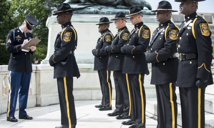 US Army Sargent Simon Smith (L) judges members of the Dekalb County Police during the 11th annual honor guard competition on Capitol Hill in Washington on May 14, 2013. The competition was held as part of the 2013 Police Week.    AFP PHOTO/Brendan SMIALOWSKI        (Photo credit should read BRENDAN SMIALOWSKI/AFP/Getty Images)