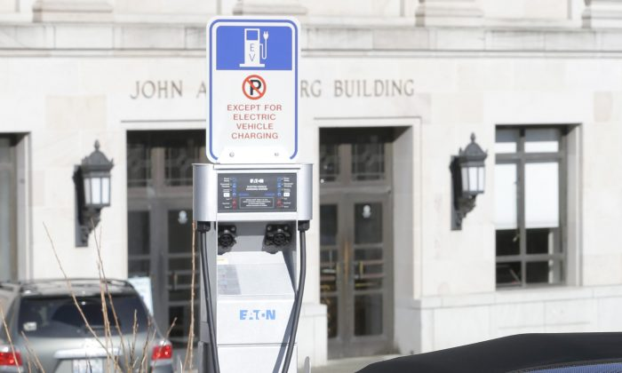 A Tesla electric car is plugged in while parked at a parking spot reserved for charging electric vehicles at the Capitol in Olympia, Wash., on Feb. 17, 2015.  (Ted S. Warren/AP Photo)