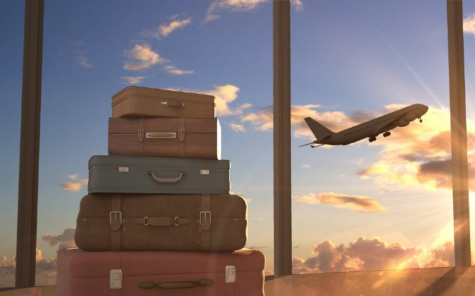 Travel bags and airplane in sky via Shutterstock*