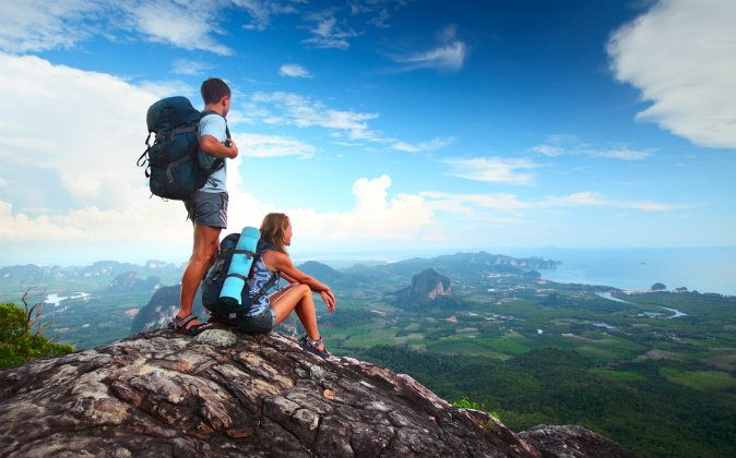 Young tourists with backpacks enjoying valley view via Shutterstock*