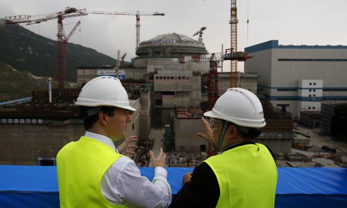 British Chancellor of the Exchequer George Osborne (L) speaks with Taishan Nuclear Power Joint Venture general manager Guo Liming in front of a nuclear reactor under construction at a nuclear power plant in Taishan, Guangdong province, on October 17, 2013. The Chinese regime is trying to win several contracts to build nuclear power facilities in other countries. (BOBBY YIP/AFP/Getty Images)