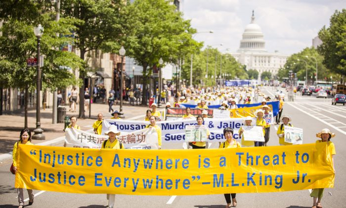 Falun Gong practitioners march in a parade calling for an end to the persecution in China, as the U.S. Capitol building is in the background, in Washington, D.C., on July 17, 2014. (Edward Dai/Epoch Times)