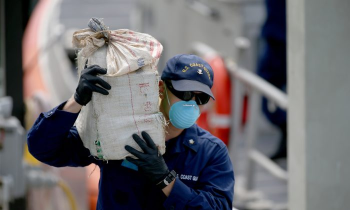A U.S. Coast Guard member helps offload bags of seized cocaine worth an estimated WHOLESALE value of more than $23 million in Miami Beach, Fla., on Sept. 18, 2014. The Coast Guard is part of the Dept. of Homeland Security. (Joe Raedle/Getty Images)