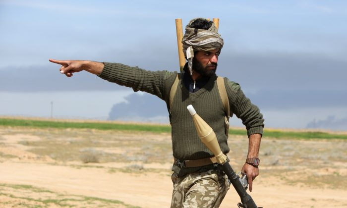 An Iraqi Shiite fighter and member of Iraq's Popular Mobilisation units supporting Iraqi government forces in the battle against the Islamic State (IS) points in the village of Albu Ajil, east of the northern city of Tikrit, on March 8, 2015 during a military operation to regain control of the Tikrit area. Some 30,000 Iraqi security forces members and allied fighters launched an operation to retake Tikrit at the beginning of March, the largest of its kind since Islamic State (IS) group forces overran swathes of territory in June. AFP PHOTO / AHMAD AL-RUBAYE        (Photo credit should read AHMAD AL-RUBAYE/AFP/Getty Images)