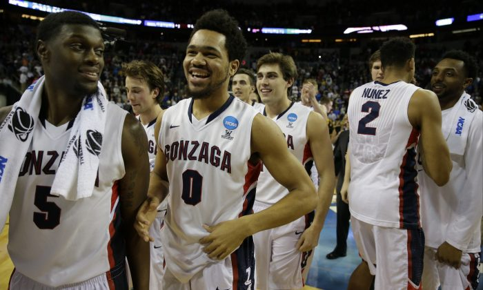 Gonzaga players including Silas Melson (0) celebrate after they beat Iowa 66-53 in an NCAA tournament college basketball game in the Round of 32, Sunday, March 22, 2015, in Seattle. (AP Photo/Ted S. Warren)
