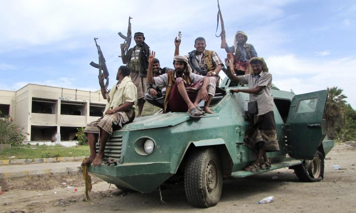 In this Friday, March 20, 2015 file photo, militiamen loyal to President Abed Rabbo Mansour Hadi ride on an army vehicle on a street in Aden, Yemen.(AP Photo/Yassir Hassan)