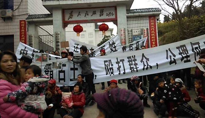 """Villagers who lost land without any compensation hung banners in front of Fenglin Township government building. The banner in the front reads: """"Our land was taken forcibly, our villagers were beaten, where is justice?"""" (Photo provided by villagers of Fenglin Town, Hubei Province)"""