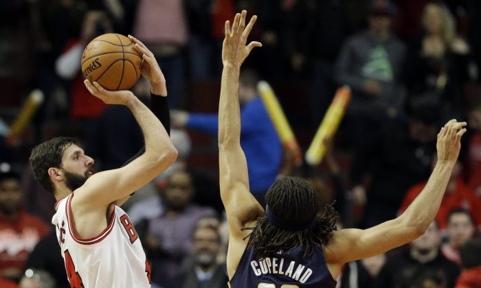 Chicago Bulls forward Nikola Mirotic, left, shoots over Indiana Pacers forward Chris Copeland during the second half of an NBA basketball game in Chicago on Wednesday, March 18, 2015. The Bulls won 103-86. (AP Photo/Nam Y. Huh)