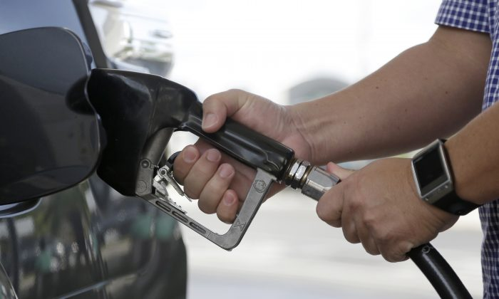 In this Jan. 23, 2015 photo, a motorist refuels his vehicle at a Westar gas station in Miami. (AP Photo/Lynne Sladky)