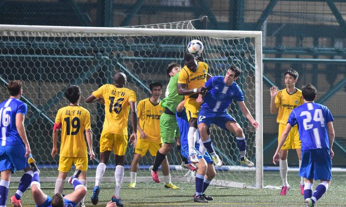Metro Gallery Sun Source (yellow) defenders clear a corner in their 3-2 first division defeat of HKFC in the HKFA League division 1 match at Sports Road on Saturday March 21, 2015. (Bill Cox/Epoch Times)