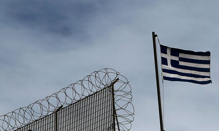 The Greek flag flutters atop a building in Athens on March 1, 2015. (Angelos Tzortzinis/AFP/Getty Images)