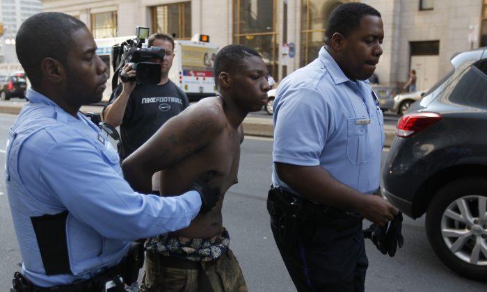 Philadelphia Police officers detain a suspect Thursday, March 22, 2012, in Philadelphia. (AP Photo/Matt Rourke)
