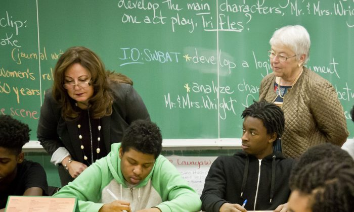 Aimee Horowitz, second from left, and and Schools Chancellor Carmen Fariña, far right, visit a 12th grade English class at Boys and Girls High School, Tuesday, March 10, 2015, in the Brooklyn borough of New York.  (AP Photo/Bebeto Matthews)