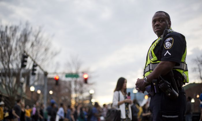 A police officer stands guard during a protest against the shooting death of Anthony Hill by police, Wednesday, March 11, 2015, in Decatur, Ga. (AP Photo/David Goldman)