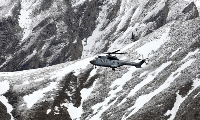 A French army helicopter heads to the Germanwings flight crash site near Seyne-les-Alpes, Wednesday, March 25, 2015, after the jetliner crashed Tuesday in the French Alps. French investigators cracked open the badly damaged black box of a German jetliner on Wednesday and sealed off the rugged Alpine crash site where 150 people died when their plane on a flight from Barcelona, Spain to Duesseldorf, Germany, slammed into a mountain. (AP Photo/Laurent Cipriani)