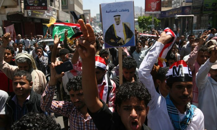 Yemenis hold a poster of the King of Saudi Arabia Salman as they chant slogans during a rally to show support for Saudi-led airstrikes against Shiite rebels, known as Houthis, in Taiz, Yemen, on Thursday, March 26, 2015. (AP Photo/Anees Mahyoub)