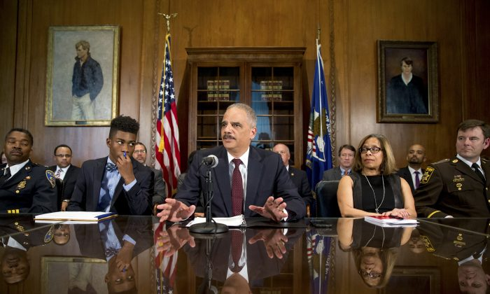 Attorney General Eric Holder, center, at a press conference held at the Department of Justice on Thursday, March 12, 2015, in Washington, D.C. (AP Photo/Andrew Harnik)