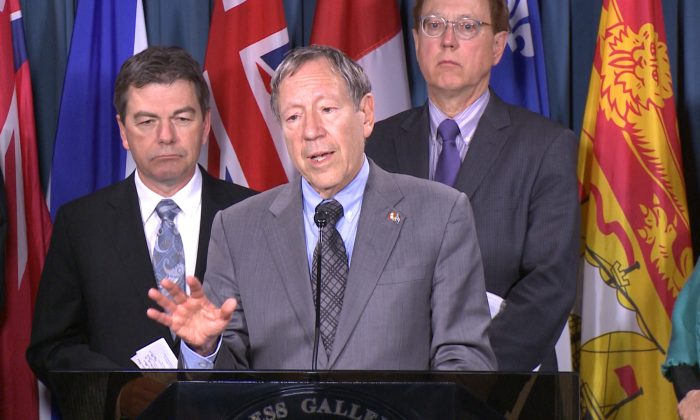 Liberal MP Irwin Cotler (C), flanked by Conservative MP David Anderson (L) and NDP MP Murray Rankin speaks during a press conference on Parliament Hill March 25, 2015. A motion by Cotler that would allow sanctions against those responsible for the detention, torture, and death in prison of Russian lawyer Sergei Magnitsky, as well as against foreign nationals responsible for human rights violations, has been unanimously adopted by the House of Commons. (NTD Television)