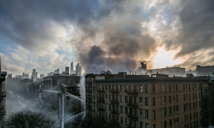 Firefighters on scene in the East Village on March 26, 2015, after a fiery building collapse. About 250 firefighter dealt with the explosion that caused a dozen injuries and the adjacent building to collapse. (Samira Bouaou/Epoch Times)