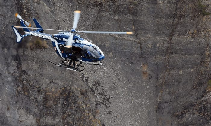 A French gendarmerie's helicopter lifts an investigator on March 26, 2015 near scattered debris on the crash site of the Germanwings Airbus A320 that crashed in the French Alps above the southeastern town of Seyne. (Anne-Christine Poujoulat/AFP/Getty Images)