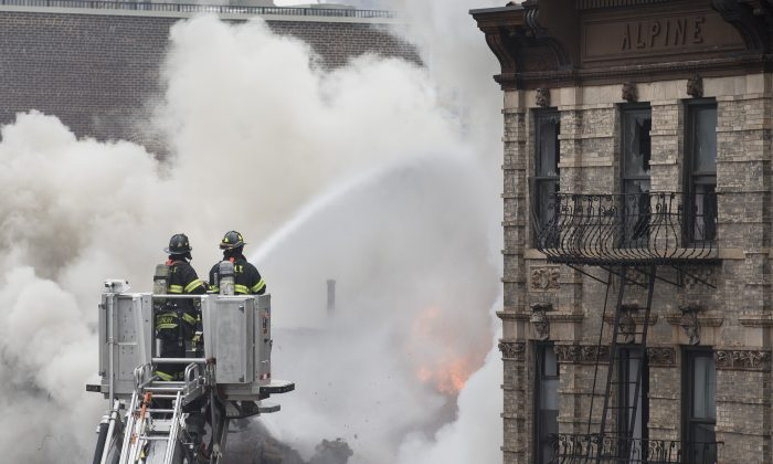 Firefighters spray water on a collapsed building in New York's East Village, Thursday, March 26, 2015, in New York. (AP/John Minchillo)