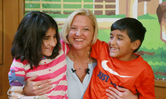 "Lynette Austin, known as ""Captain Sam,"" poses with war victims, Shah Bibi Tarakhail, left, and Abdul Wahid, during a media event at Shriners Hospitals for Children in Los Angeles, March 27, 2015. (AP Photo/Nick Ut)"