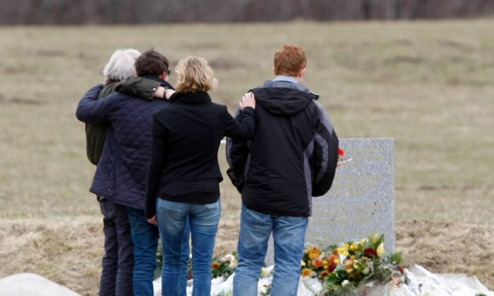 Family members of a victim pause in front of a stele, a stone slab erected as a monument, set up in the area where a Germanwings aircraft crashed in the French Alps, in Le Vernet, France, March 28, 2015. (AP Photo/Claude Paris)