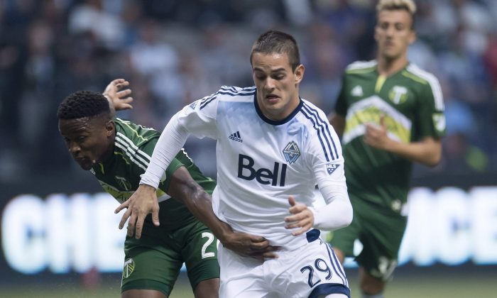 Vancouver's Octavio Rivero fights for control of the ball with Portland's George Fochive in Vancouver on March 28, 2015. Rivero was held off the scoresheet for the first time in four games against Portland. (The Canadian Press/Jonathan Hayward)