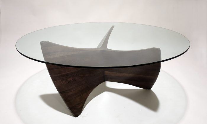 "This photo provided by Aaronscottdesign.com shows a coffee table of walnut and glass designed by Aaron Scott, who began experimenting with stacked and laminated wood about ten years ago. ""I liked the idea of making wood a purely plastic medium, where curvature could occur along any axis,"" Scott said. (AP Photo/Aaronscottdesign.com)"