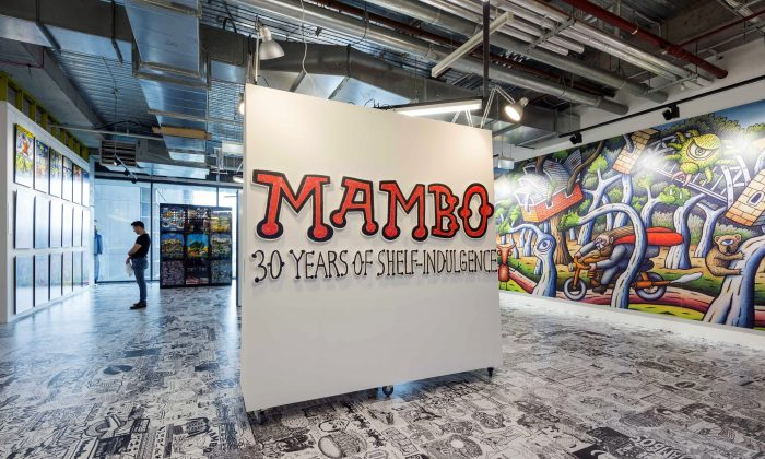 """The entrance to the Mambo exhibition at aMBUSH GALLERY. In the background is part of the """"Millennial Wallscape"""" a Reg Mombassa mural commissioned to celebrate the recent 40th anniversary of the Sydney Opera House. It was painted on a construction hoarding for a building site in the Opera House's southern forecourt. (Courtesy of aMBUSH Gallery)"""