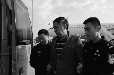 Pang Shunxi (C) is brought back to China by a security detail on March 28, 2015. (Larry Ong/Epoch Times)