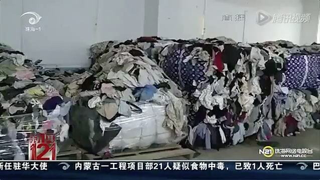 A screenshot from the News 121 program, aired on Zhuhai Television, shows tons of clothing being imported to China, allegedly originating from landfill and hospital morgues. (Screenshot/Epoch Times)