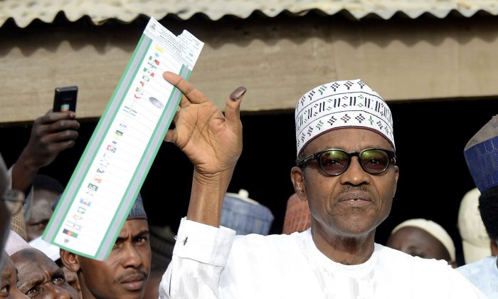 "Main opposition All Progressives Congress (APC) presidential candidate Mohammadu Buhari holds his ballot paper prior to casting his vote at a polling station in the ""Gidan Niyam Sakin Yara A ward"" at Daura in Katsina State on March 28, 2015.  (Pius Utomi Ekpei/AFP/Getty Images)"