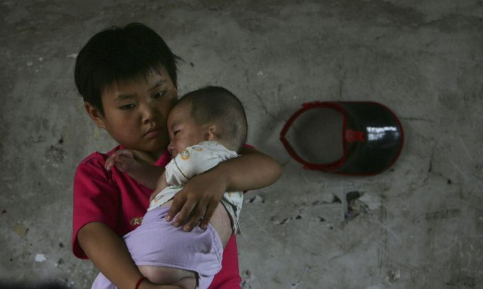 Wang Huaixue holds a baby at Wang Jiayu Orphanage on July 9, 2006 in Anhui Province. Millions of official and unofficial orphans are the victims of a Chinese social system. (China Photos/Getty Images)