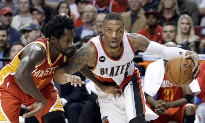 Portland Trail Blazers guard Damian Lillard, right, drives on Houston Rockets guard Patrick Beverley during the second half of an NBA basketball game in Portland, Ore., Wednesday, March 11, 2015. Portland won 105-100. (AP Photo/Don Ryan)