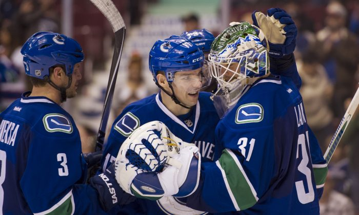 Goalie Eddie Lack is congratulated by teammates Radim Vrbata and Kevin Bieksa after the Vancouver Canucks defeated the Winnipeg Jets on March 24, 2015 at Rogers Arena in Vancouver. (Rich Lam/Getty Images)