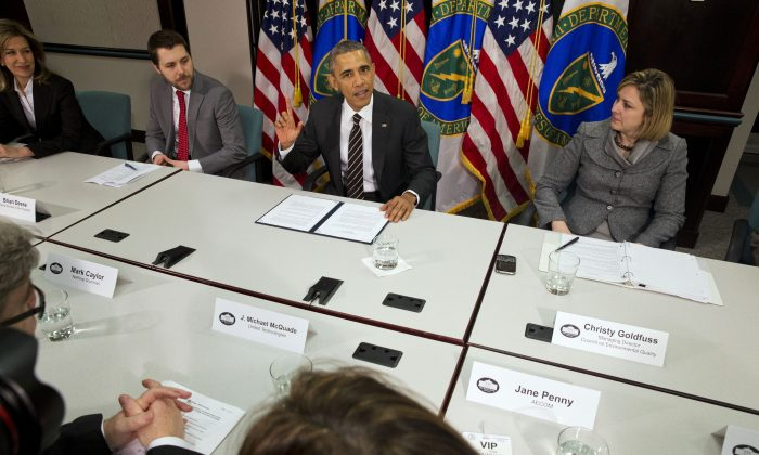 In this March 19, 2015, file photo, President Barack Obama, flanked by senior adviser Brian Deese, left, and Christina Goldfuss, managing director of the Council on Environmental Quality, speaks at Energy Department in Washington. In a highly anticipated announcement, the United States will pledge to cut its greenhouse gas emissions by up to 28 percent as its contribution to a major global climate treaty nearing the final stages of negotiation, according to people briefed on the White House's plans. (AP Photo/Jacquelyn Martin)
