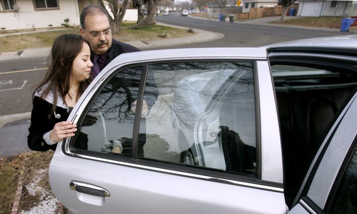 Sgt. Vincent Matranga, of the Sacramento City Unified School District, places Lydia Ochoa, 15, into his patrol car in Sacramento, Calif., on Jan. 30, 2007. (AP Photo/Rich Pedroncelli)