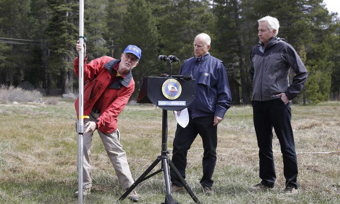 Frank Gehrke, left, chief of the California Cooperative Snow Surveys Program for the Department of Water Resources, points to a mark on the snow pack measuring pole that was the lowest previous snow pack level as Gov. Jerry Brown, center and Mark Cowin, director of the Department of Water Resources look on at a news conference near Echo Summit, Calif., Wednesday, April 1, 2015. Gehrke said this was the first time since he has been conducting the survey at that he found no snow at this location at this time of the year. Brown took the occasion to announce that he signed an executive order requiring the state water board to implement measures in cities and towns to cut water usage by 25 percent compared with 2013 levels. (AP Photo/Rich Pedroncelli)