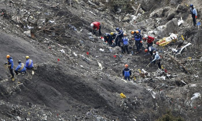Rescue workers work at debris of the Germanwings jet at the crash site near Seyne-les-Alpes, France. Investigators recovering remains from all 150 people aboard a German passenger jet that crashed into the Alps have accelerated their timeframe for identifying and matching their DNA _ whether that be from a body part or only a shred of skin. (AP/Laurent Cipriani)