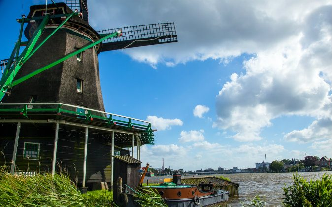 Windmill on a river with a boat, The Netherlands via Shutterstock*