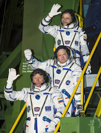 Russian cosmonaut Mikhail Kornienko of the Russian Federal Space Agency (Roscosmos (Top), NASA astronaut Scott Kelly (C), and Russian cosmonaut Gennady Padalka of Roscosmos wave farewell as they board the Soyuz TMA-16M spacecraft ahead of their launch to the International Space Station, in Baikonur, Kazakhstan, on March 27, 2015. (NASA)